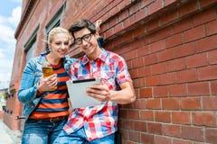 Paare an den Feiertagen Sightseeing-Tour mit Tablet-PC organisierend Stockbilder