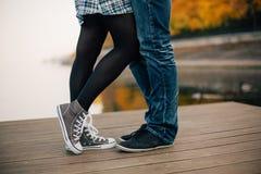 Paare in den Gummiüberschuhen, die auf dem Fluss küssen, koppeln an Stockbilder