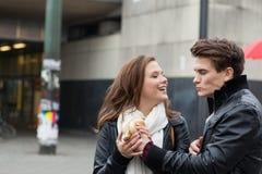 Paare in den Jacken, die Hotdog halten Lizenzfreie Stockfotos