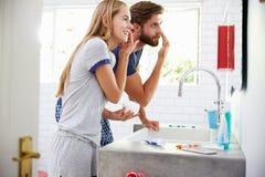 Paare in den Pyjamas, die auf Feuchtigkeitscreme in Badezimmer sich setzen Stockfotos