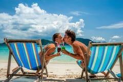 Paare in den Ruhesesseln auf einem Strand bei Thailand lizenzfreie stockfotografie