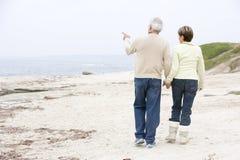 Paare an den Strandholdinghänden und -c$zeigen Stockfotografie