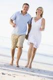 Paare an den Strandholdinghänden und -c$lächeln Lizenzfreies Stockfoto