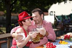 Paare in den traditionellen Kostümen in einem bayerischen Bier arbeiten im Garten Lizenzfreie Stockbilder