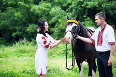 Paare in den ukrainischen Kostümen mit einem Pferd Lizenzfreie Stockfotografie