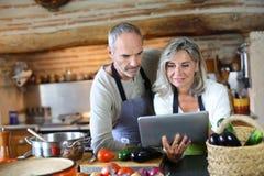 Paare in der alten Küche, die nach Rezept sucht Stockfotografie