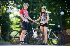 Paare in der cyling Kleidung, die nahe ihren Fahrrädern aufwirft stockbilder