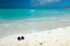 Paare der farbigen Sandalen auf einem weißen Sand setzen auf den Strand Stockbilder