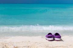Paare der farbigen Sandalen auf einem weißen Sand setzen auf den Strand Lizenzfreie Stockfotografie