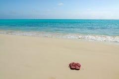 Paare der farbigen Sandalen auf einem weißen Sand setzen auf den Strand Stockfotografie