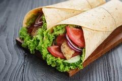 Paare der frischen saftigen Verpackungssandwiche mit Huhn und Gemüse Stockbilder