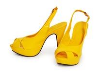 Paare der gelben weiblichen Schuhe getrennt auf Weiß Stockfotos