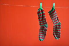 Paare der gestreiften Socken, die an einem Seil lokalisiert auf Rot hängen Stockbilder
