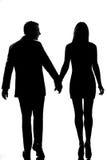 Paare der hinteren Ansicht eine, die Hand in Hand gehen Lizenzfreie Stockfotos