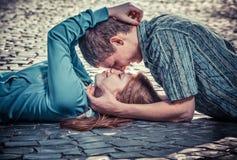 Paare der Jugendlichen, die zusammen in der Straße liegen Stockfotos