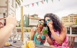 Paare der jungen Frauen, die gesunde Getränke trinken Stockfotografie