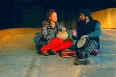 Paare der jungen Musiker, die im Boden sitzen Stockbild