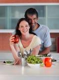 Paare in der Küche, die an der Kamera lächelt Stockfotos