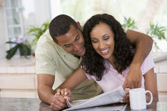 Paare in der Küche mit Zeitung und einem Kaffee Stockbild