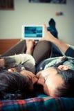 Paare in der Liebe auf dem Bett unter Verwendung der Tablette lizenzfreie stockfotografie