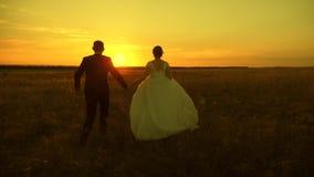 Paare in der Liebe auf einer Flitterwochenreise Braut und Br?utigam Langsame Bewegung Paar im Liebesh?ndchenhalten geht zum Sonne stock video