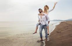 Paare in der Liebe auf Strandsommerferien Frohes M?dchen, das auf dem jungen Freund hat Spa? huckepack tr?gt lizenzfreies stockfoto