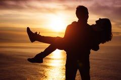 Paare in der Liebe bei dem Sonnenuntergang, der Spaß hat stockfotografie
