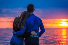 Paare in der Liebe bei Sonnenuntergang durch das Meer Lizenzfreie Stockfotos