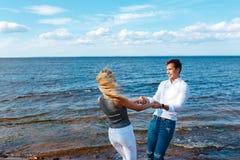 Paare in der Liebe, die den Spaß lacht und lächelt am Strand hat Lizenzfreie Stockfotografie