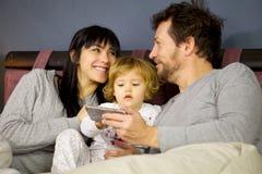 Paare in der Liebe, die einander im Bett mit Tochter betrachtet Lizenzfreies Stockbild