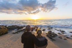 Paare in der Liebe, die einen Sonnenuntergang auf dem Strand aufpasst Stockbilder
