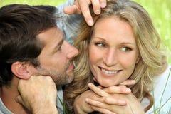Paare in der Liebe, die im Gras liegt Stockbilder