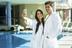 Paare in der Liebe, die nahe bei einem Pool in einer Robe steht Stockfoto