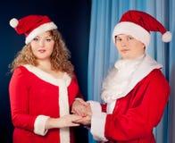 Paare in der Liebe, die Sankt-Hüte trägt, nähern sich Weihnachtsbaum. Fette Frau und nehmen Passsitz ab Lizenzfreie Stockfotos