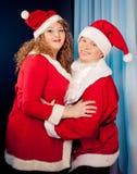 Paare in der Liebe, die Sankt-Hüte trägt, nähern sich Weihnachtsbaum. Fette Frau und nehmen Passsitz ab Stockbild