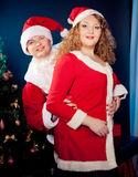 Paare in der Liebe, die Sankt-Hüte trägt, nähern sich Weihnachtsbaum. Fette Frau und nehmen Passsitz ab Lizenzfreies Stockfoto