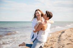 Paare in der Liebe, die Spaß auf dem Strand lacht und hat Stockfoto