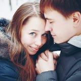 Paare in der Liebe, die Spaß im Winterwald umarmt und hat Stockbilder