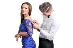 Paare in der Liebe, die zur Partei geht, hilft es, Kleid an zu setzen Stockbild