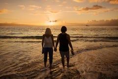 Paare in der Liebe, die zusammen entlang den Strand bei Sonnenuntergang geht Stockbilder