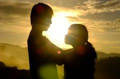 Paare der Liebe stehen und umarmen und Blickkontakt im Nebel auf dem Berg bei dem Morgen und dem Sonnenaufgang hinter ihnen Lizenzfreie Stockfotos