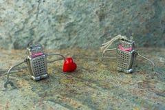 Paare in der Liebe von Robotern mit einem Herzen St.-Valentinsgruß-Tageskonzept Stockfoto