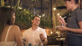 Paare in der Liebesauftragsnahrung bei Tisch während romantisches Abendessen, wenn Restaurant geglättet wird Kellnerin, die Auftr stock video