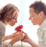 Paare der Liebhaber. Mann stellt Blume dar lizenzfreie stockbilder