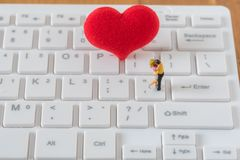 Paare der Miniaturzahl Liebhaber und großes rotes Herz auf weißem Baut. lizenzfreie stockbilder