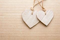 Paare der Pappe schnitten Herzen gegen gestreiftes Pappblatt Stockfotos