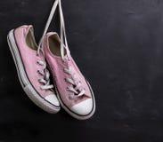 Paare der rosa Textilturnschuhe, die an einer Spitze hängen lizenzfreie stockfotos