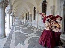 Paare von Masken unter Säulengängen in Venedig Stockfotos