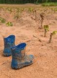 Paare der schmutzigen Stiefel, die im Schlamm in der Manioka bedeckt werden, bewirtschaften stockfotografie