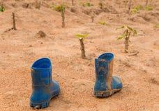 Paare der schmutzigen Stiefel, die im Schlamm in der Manioka bedeckt werden, bewirtschaften lizenzfreie stockfotografie